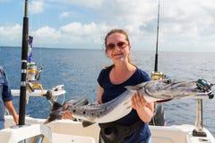 Wooman at deep sea fishing. Lucky young wooman holding barracuda on boat deck at deep sea fishing Royalty Free Stock Image