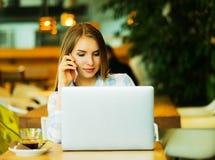 Wooman di affari facendo uso del computer portatile al caffè Giovane bello sitti della ragazza Immagine Stock