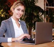 Wooman di affari facendo uso del computer portatile al caffè Giovane bello sitti della ragazza Immagini Stock