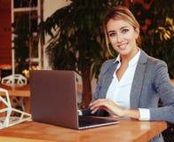 Wooman di affari facendo uso del computer portatile al caffè Giovane bello sitti della ragazza Immagini Stock Libere da Diritti