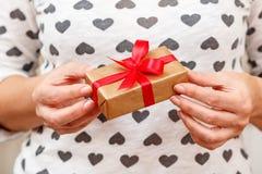 Wooman die een giftdoos houden bond met een rood lint in haar handen Ondiepe velddiepte, Selectieve nadruk op de doos Concept van stock afbeeldingen