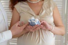 Wooman grávido, montantes das peúgas das crianças nas mãos da mamã, as mãos da mamã com montantes fotografia de stock royalty free