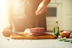 Wooman hands cutting beef meat on wooden chopping board, rosemary, oil, salt, pepper. Girk cooking pork meat on white. Kitchen backgound. Copy space. Sunlight Royalty Free Stock Images