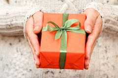 Woman holding a gift box tied with a green ribbon in her hands. Shallow depth of field, Selective focus on the box. Concept of giving a gift on holiday or royalty free stock image