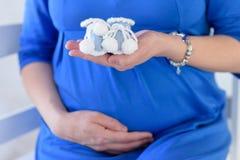 Wooman incinto, bottini dei calzini dei bambini sulle mani della mamma, le mani della mamma con i bottini fotografia stock libera da diritti