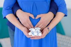 Wooman incinto, bottini dei calzini dei bambini sulle mani della mamma, le mani della mamma con i bottini immagine stock