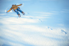 Wooman making Snow angel. In sunny day Royalty Free Stock Image
