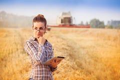 Wooman piacevole dell'agricoltore che pensa nel giacimento di grano Immagine Stock