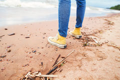 Wooman sneakers on the beach. Sea waves at a sand. Wooman's sneakers on the beach. Sea waves at a sand. Cloudy sky. Sea foam on the coast. Reflection in the wet royalty free stock photos