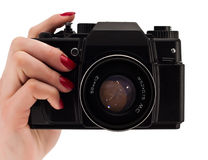 Woomans hand with red nails holding a camera. Isolated on white royalty free stock photography