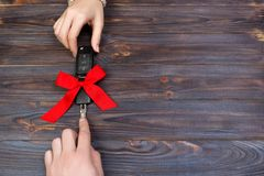 Woomen give car key. Woman hand hold car key with red bow. Giving a car as a gift Stock Photography
