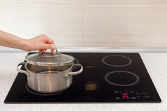 Woomen hand open a saucepan in modern kitchen with induction stove. Stock Photography