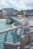 Woomen on pier near beach with roofed wicker chairs in Travemuende at the Baltic Sea. Travepromenade in Travemunde, a Royalty Free Stock Images