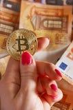 woomens hand med bitcoin och 50 femtio euro av bakgrunder fakturerar sedlar Royaltyfri Fotografi