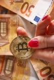 woomens hand med bitcoin och 50 femtio euro av bakgrunder fakturerar sedlar Arkivbilder