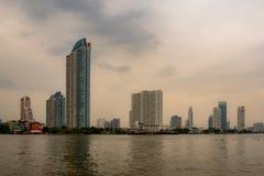 Woon, commerciële en bedrijfsgebouwen naast de rivier met donkere hemel stock foto