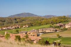 Woon huizen op een heuvelige golfcursus stock afbeeldingen