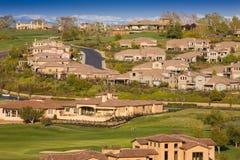 Woon huizen op een heuvelige golfcursus Stock Afbeelding