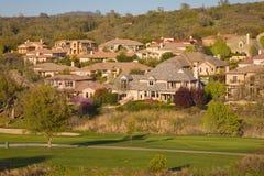 Woon huizen op een heuvelige golfcursus Stock Fotografie
