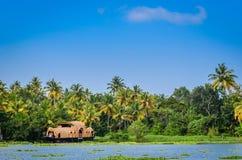 Woonboot in binnenwateren van Kerala tegen dik groen en B stock foto