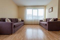 woonkamer met een bank, vensters en gordijnen Royalty-vrije Stock Foto