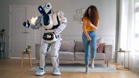 Woonkamer met een dame en een robot die vreugdevol dansen stock footage