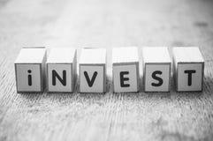 woord op houten kubus op houten bureauconcept als achtergrond - investeer stock afbeelding