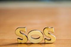 Woord` sos ` van houten brieven wordt gemaakt die stock fotografie