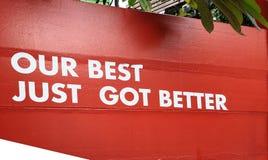 Woord van de sticker is het witte kleur een Ons beste enkel geworden beter op rode muur voor de zaken van de successiedienstenind royalty-vrije stock afbeelding