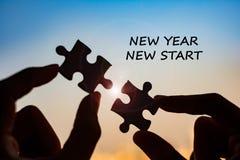 Woord van het nieuwjaar het Nieuwe Begin met handen die het stuk van het paarraadsel verbinden tegen zonsopgangeffect, de figuurz stock fotografie