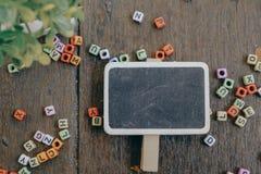 woordblok en groene installatie op houten achtergrond Stock Foto's