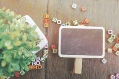 woordblok en groene installatie op houten textuur als achtergrond met sunhazeeffect Stock Foto's