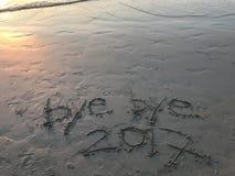 """Woorden """"bye tot ziens 2017† op het strand met mooi oranje licht van zonsondergang stock foto's"""