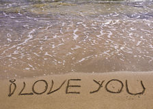 Woorden I LIEFDE U geschreven op zand, met golven op achtergrond royalty-vrije stock fotografie