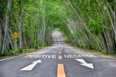 Woorden van positief en negatief op weg stock fotografie