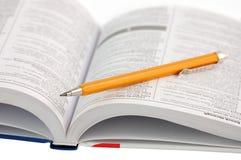 Woordenboek met potlood stock foto