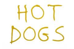Woordenhotdogs met mosterd worden geschreven die Stock Afbeeldingen