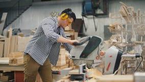 Woordworker die met elektrisch zaag bezig zagend hout werken in workshop stock video