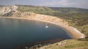 Worbarrow Bay east of Lulworth Cove and near Tyneham on the Dorset coast England uk with a yacht stock footage