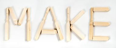 The word «make» written in letters of wooden bars royalty free stock photos