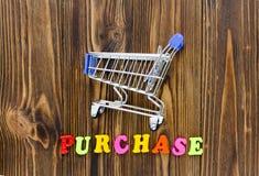Word ` aankoop ` en leeg boodschappenwagentje op houten achtergrond stock foto