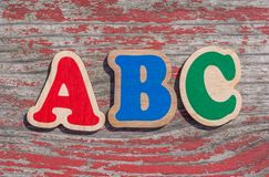 Word ABC made of wooden letters. On shabby wood background stock image