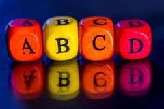 Word `abcd` of the colored wooden cubes. On dark background stock images