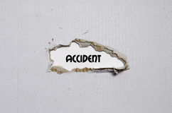 The word accident appearing behind torn paper. The word accident behind torn paper Stock Image