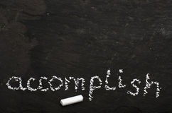The word accomplish written with chalk on black stone. Word accomplish written with chalk on black stone stock images
