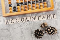 Word ACCOUNTANT laid out of handwritten letters on cardboard squares near old wooden abacus and three cones. On gray cracked concrete stock image