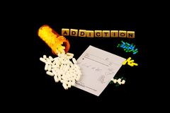 Addiction spelled out with tiles above spilled white pills over a prescription pad and colored pills on a black background. The word addiction is spelled out in Royalty Free Stock Photo