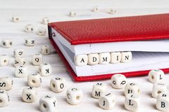 Word Admin written in wooden blocks in red notebook on white woo stock photography