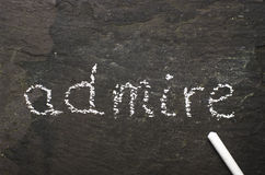 The word admire written with chalk on black stone. Stock Photo
