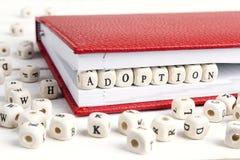Word Adoption written in wooden blocks in notebook on white tabl Stock Photos